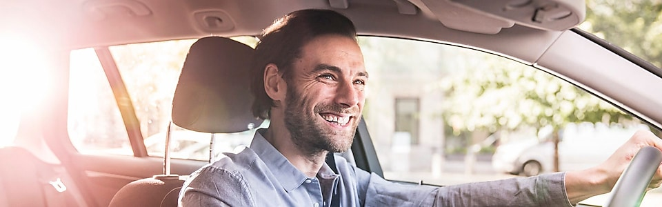 Smiling man behind driving wheel